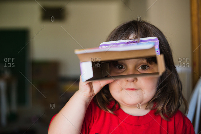 Girl looking through cereal box