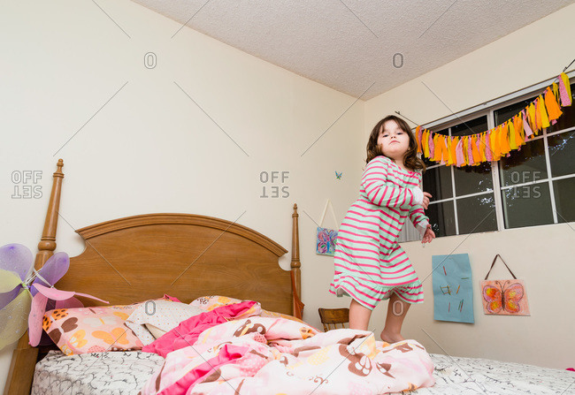 Girl in nightgown jumping on bed