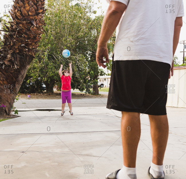 Girl jumping for ball with man