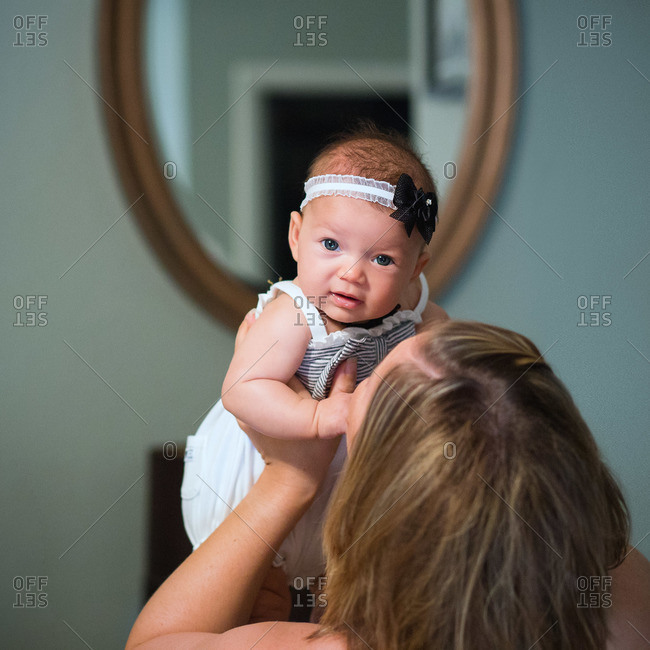 Mom holding up baby with bow