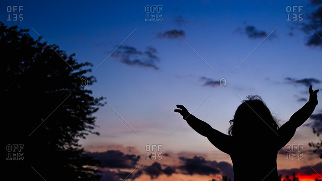 Girl with arms raised in silhouette