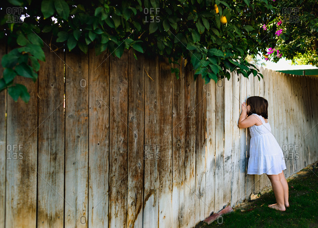 Girl looking through backyard fence