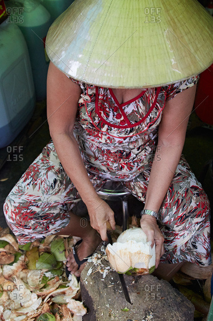 Woman cutting up a coconut