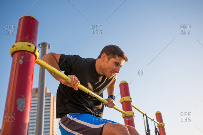Man doing exercise on outdoor bar