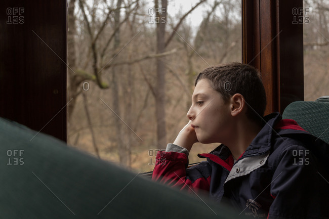 Boy staring out a train window