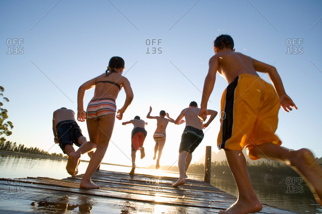 Children jumping from jetty into lake at sunset, rear view