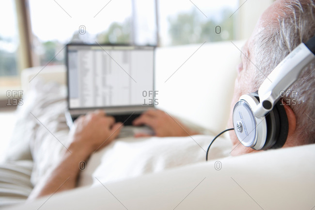 Senior man relaxing on sofa at home, listening to music on headphones, using laptop, rear view