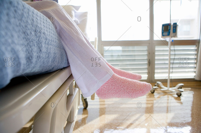 Female patient wearing pink slippers, sitting on hospital bed, low section