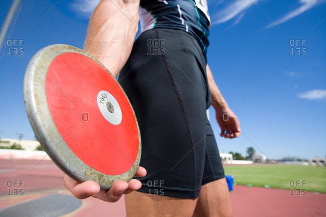 Male athlete with discus, mid section