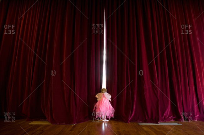 Ballerina girl with fairy wings peeking through stage curtains, rear view