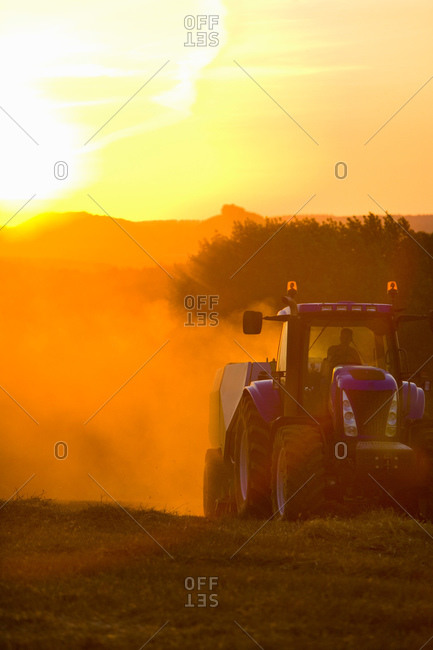 Tractor straw baling in sunny, rural field