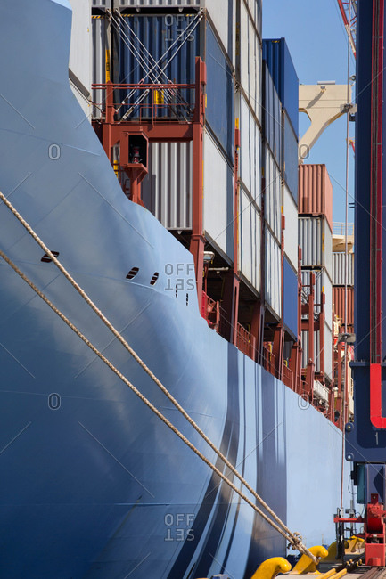 Container ship with cargo containers moored at commercial dock