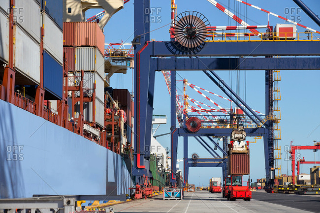 Crane loading cargo container onto container ship at commercial dock