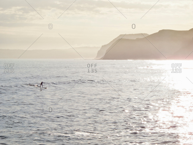 Man riding a wave whilst paddle surfing in picturesque location