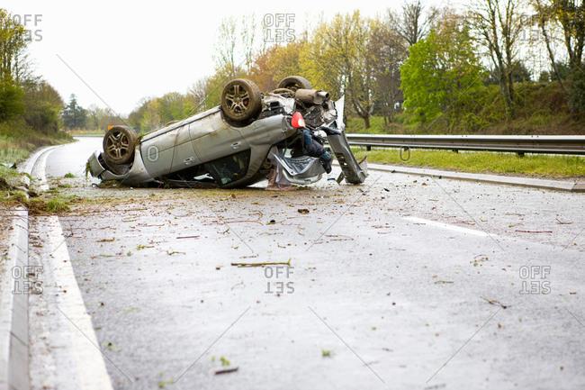 Upside down crashed car on motorway