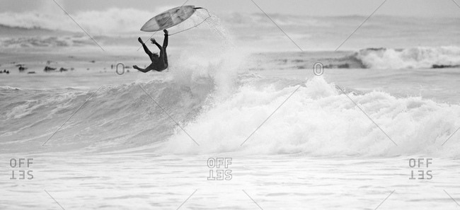 Surfer falling off surfboard on wave