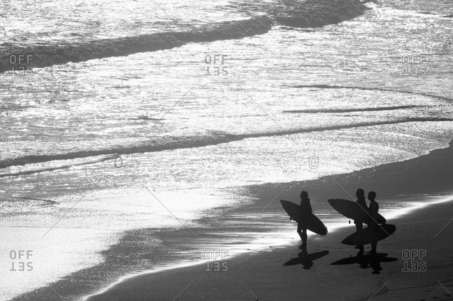Group of Surfers carrying surf boards looking out to sea