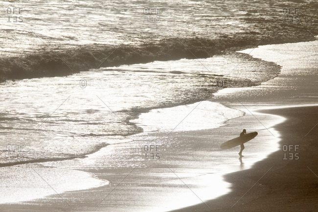 Surfer carrying surf board, walking along beach from sea