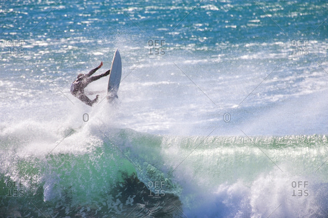 Surfer falling off surfboard on crashing wave