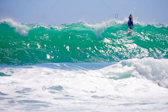 Surfer paddling through wave on surfboard
