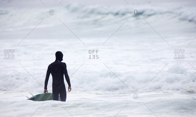 Man holding surfboard looking out to sea