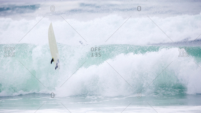 Loose surfboard on large wave