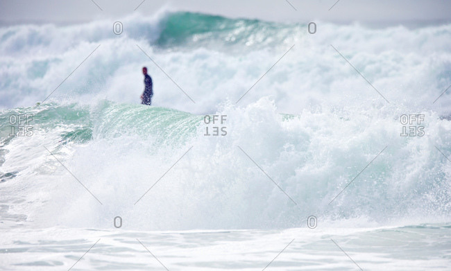 Distant surfer standing on surfboard
