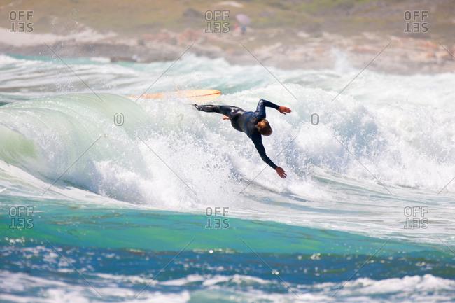 Surfer falling off surfboard on wave