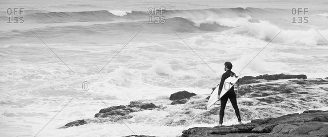 Man with surfboard standing on rocks looking out to sea