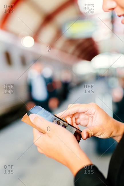 Businesswoman using smart phone at railroad station