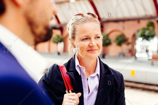 Businesswoman standing with colleague at railroad station