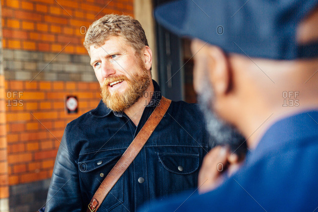 Businessman talking to colleague outside railroad station