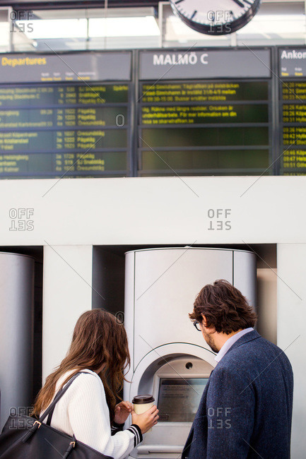 Business colleagues using ticket machine at railroad station