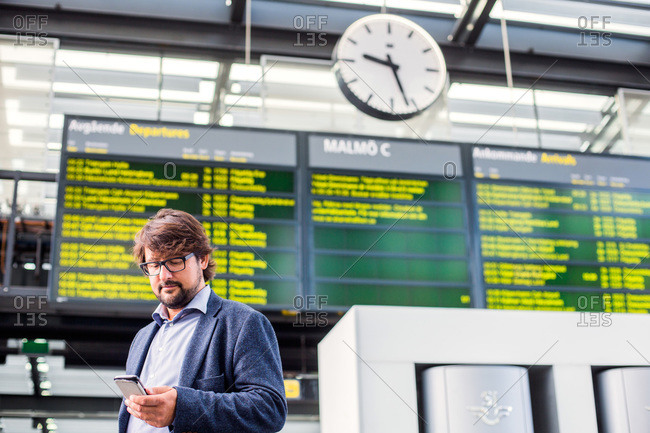 Businessman using smart phone at railroad station