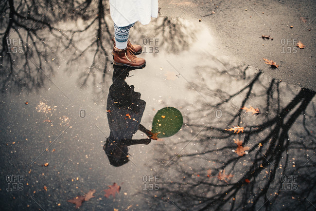 Girl playing with a balloon reflected in a puddle