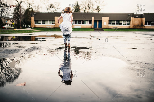 Little girl playing in a puddle near a school