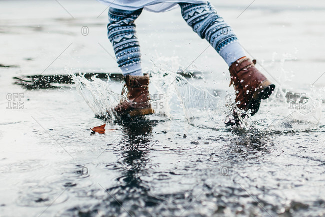 Feet of a little girl splashing in a puddle