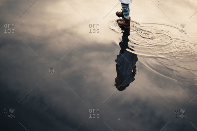 Little girl walking through a puddle