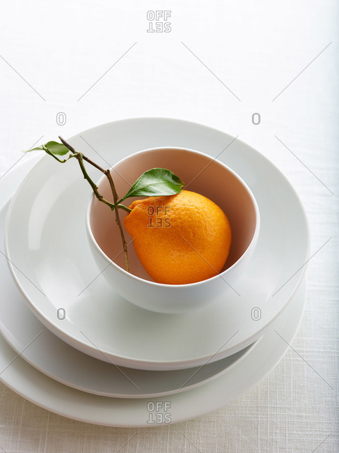 Single orange in a white ceramic bowl