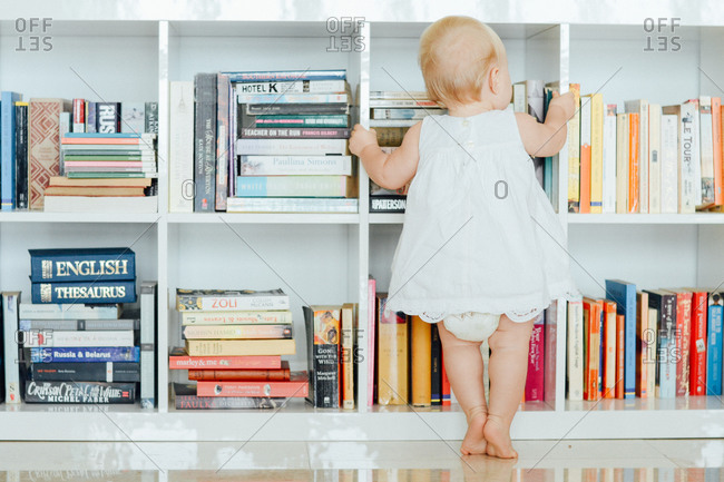 Baby holding a bookshelf while standing