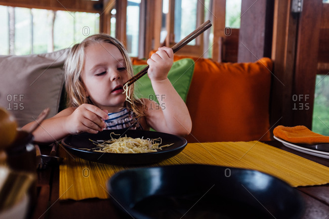 Girl eating noodles with chopsticks