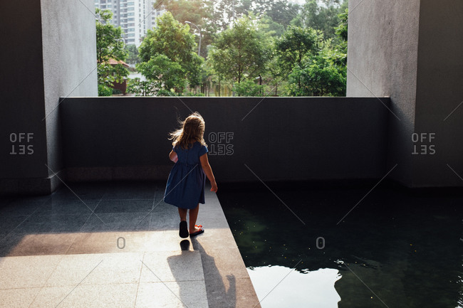 Girl standing at an urban modern swimming pool