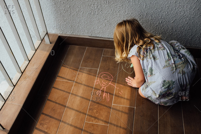 Girl drawing on the floor with chalk