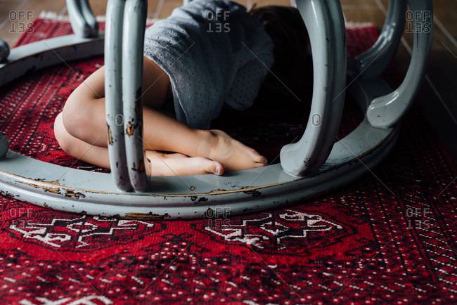 Girl hiding under a piece of furniture