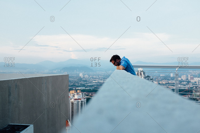 Man looking down from roof deck