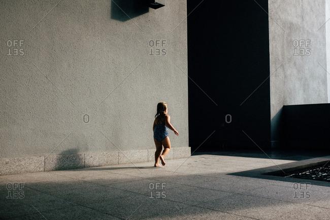 Girl running next to a modern swimming pool