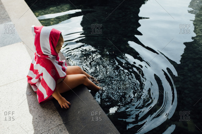 Girl sitting at the edge of a modern swimming pool