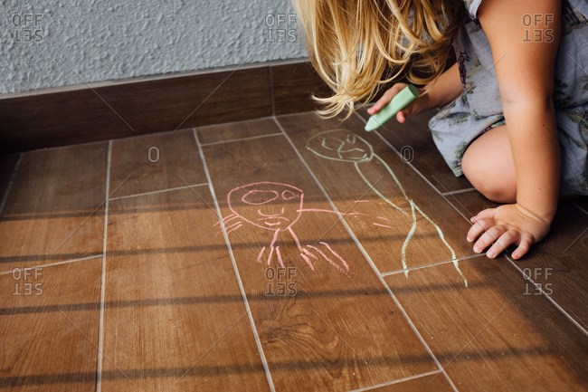 Girl making chalk drawings on the floor