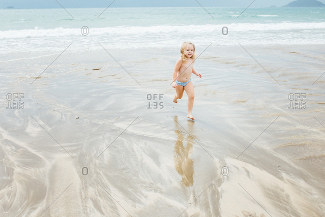 Girl running from the surf at the beach