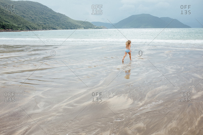 Girl running toward the water on the beach